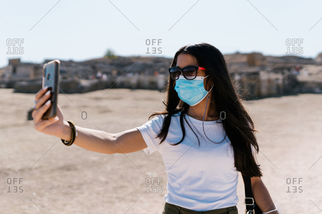 Young female in protective medical mask standing on sunny street and taking selfie on smartphone during coronavirus epidemic