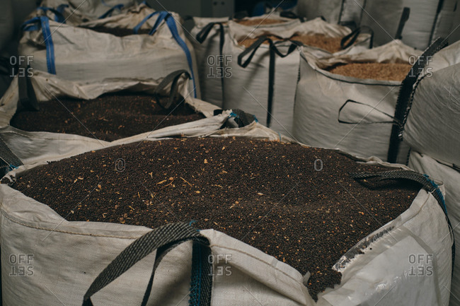 Huge bags with black grain crops stored in stock in industrial facility of factory