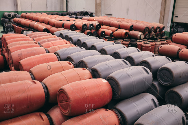 High angle of assorted plastic barrels stored in spacious warehouse in industrial area of factory