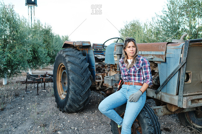 Satisfied adult female farmer sitting on wheel of agricultural machine during harvesting season on olive plantation