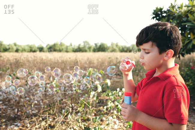 Adorable boy in summer outfit standing in park and blowing soap bubbles while having fun at weekend