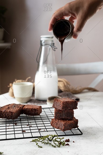 Crop hand of housewife pouring chocolate sauce from pot over stacked pieces of homemade brownie cake arranged on metal grid while preparing dessert in kitchen
