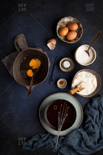Top view composition of various ingredients in bowls with kitchen utensils arranged on table during preparation of brownie cake