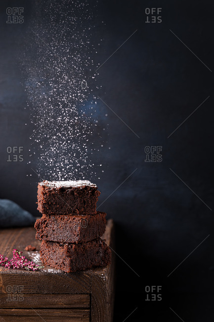 Yummy homemade chocolate brownies pieces stacked on table and sprinkled with white sugar powder against dark background