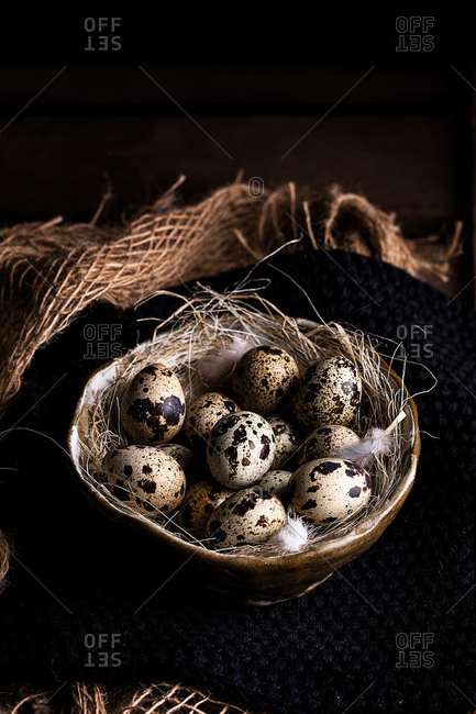 High angle of pile of quail eggs placed in straw in bowl on table in rustic kitchen