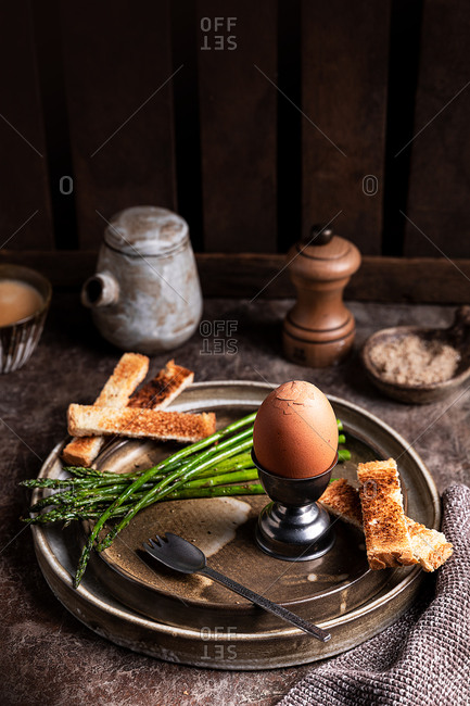 High angle of bread crouton and soft boiled egg served on table in kitchen for breakfast