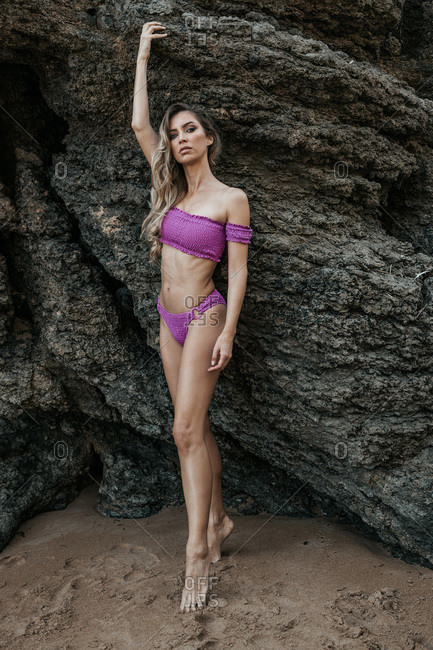Graceful slim female wearing purple bikini standing on tiptoes near rough rock at seaside and looking at camera