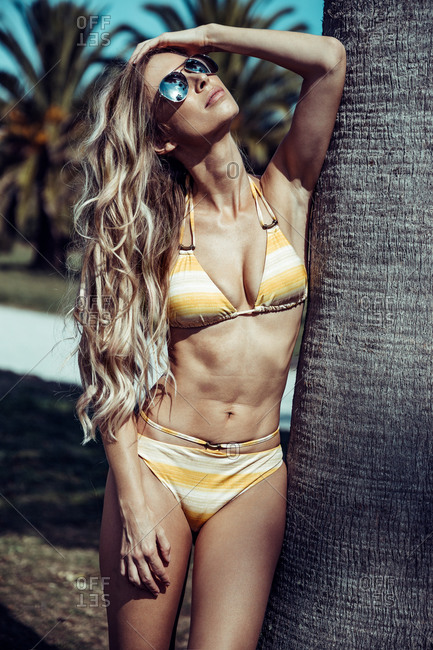 Slender female wearing bikini leaning on palm tree and enjoying summer with sunglasses on sunny day