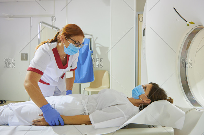 Doctor in uniform and eyeglasses using tomography machine with lying female patient in hospital
