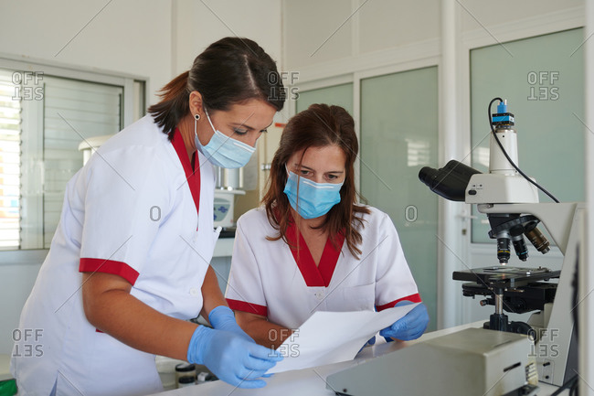 Unrecognizable female scientists in uniforms and face masks watching paper near microscope on table in laboratory