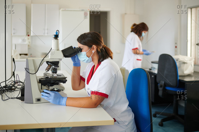 Female medical technologists in uniforms and sterile masks working with microscope in laboratory