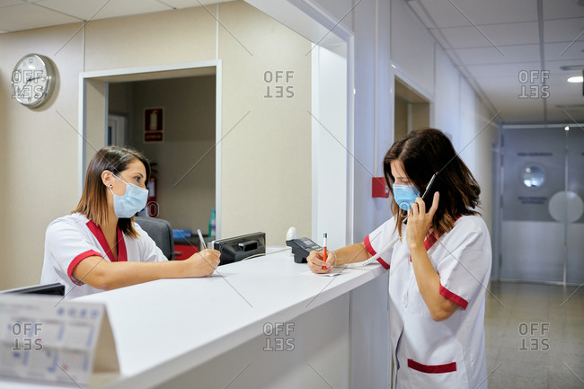 Concentrated female nurse wearing white medical suit and face mask taking notes in clinical record chart while standing near modern hospital reception