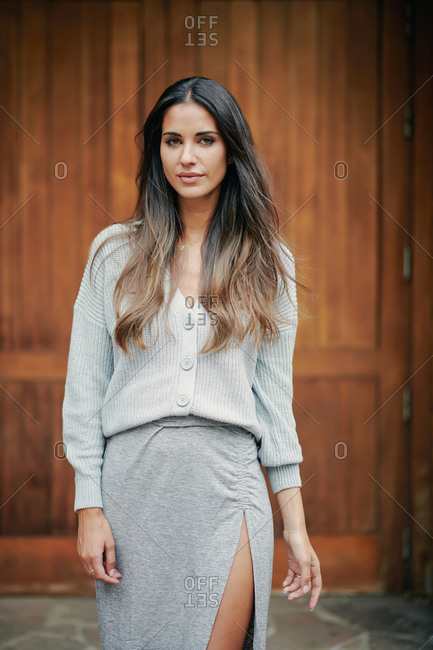 Carefree female with long brown hair and in casual dress standing near wooden doors in city and calmly looking at camera