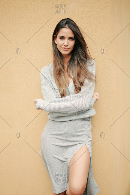 Charming female with long hair and in casual dress standing near building on street and modestly looking at camera