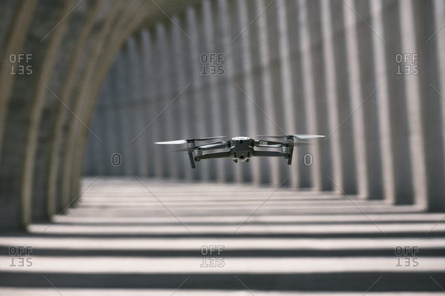 Modern drone flying in empty arched walkway with columns casting shadows in shape of lines on sunny day