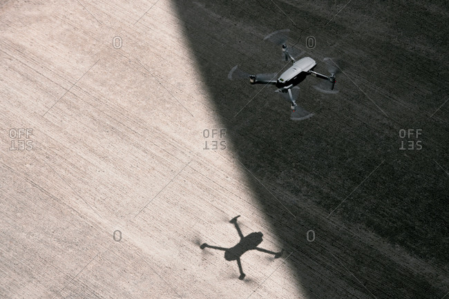 From above modern drone flying in empty concrete walkway casting shadows on sunny day