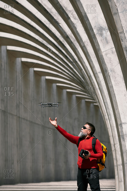 Elderly male photographer standing in archway on sunny day with modern flying drone in La Palma