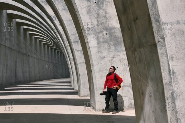 Traveling male photographer with professional photo camera taking picture of amazing arched passage in city on sunny day