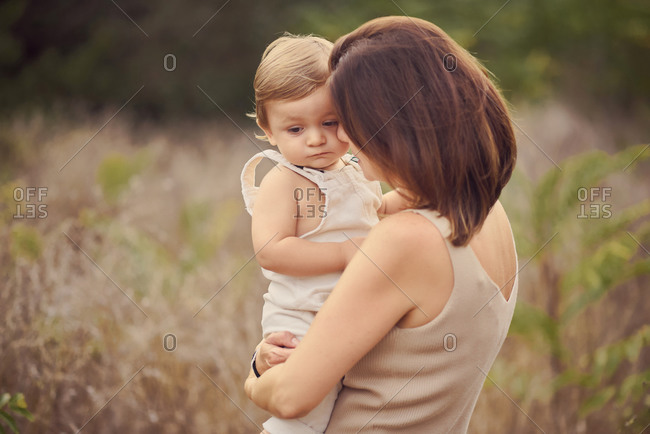 Anonymous woman embracing melancholic blond toddler child near grass in summer in daylight