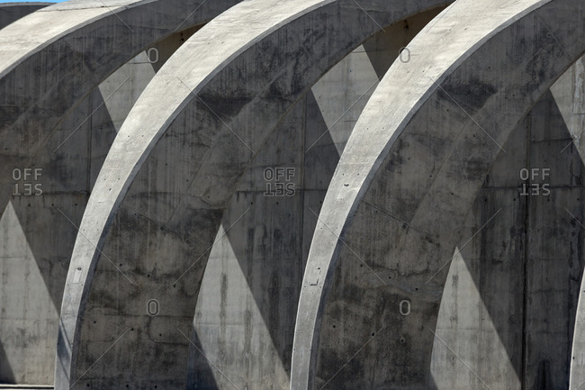 Detail of contemporary concrete construction with curved arched columns illuminated by sunlight in city