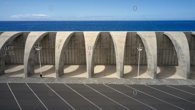 High angle of walkway with stone arched columns located near public parking on background of amazing seascape in summer