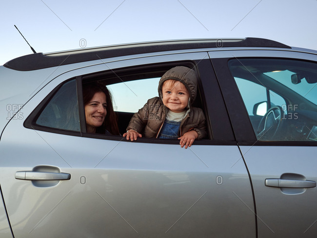 Cheerful cute toddler peering out of car window while sitting on back seat with mother and looking away