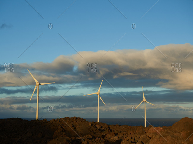 Scenic view of modern windmills located on hill against seascape at sundown in countryside