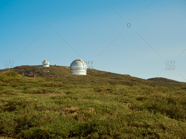 Largest optical reflecting telescope Gran Telescopio Canarias located on grassy hilltop against clear blue sky at astronomical observatory on island of La Palma in Spain