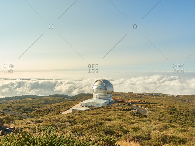 Largest optical reflecting telescope Gran Telescopio Canarias located on grassy hilltop against cloudy sky at astronomical observatory on island of La Palma in Spain