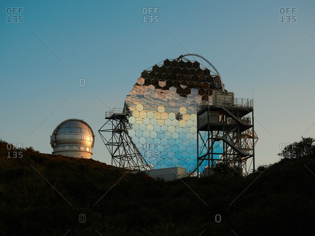 Various modern telescopes including MAGIC or Major Atmospheric Gamma Imaging Cherenkov Telescope located on hill slope at astronomical observatory on island of La Palma in Spain
