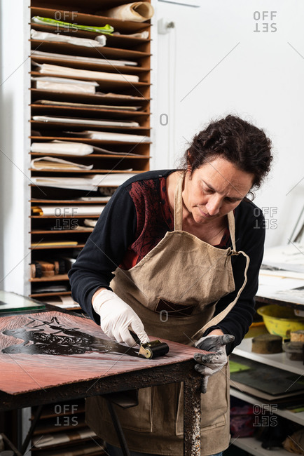 Mature female artist in apron and gloves covering engraved plate with ink while creating artwork in professional workroom
