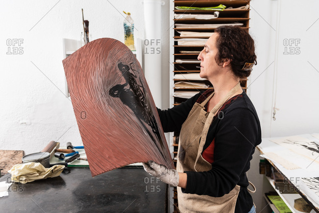 Side view of concentrated middle aged craftswoman holding piece of linoleum with inked pattern while making print in creative workplace