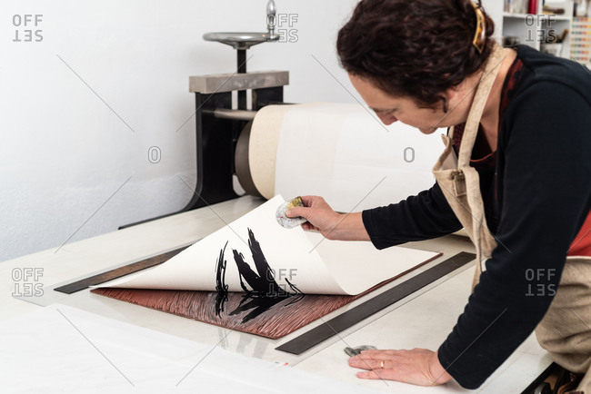 Side view of skilled female artist removing paper sheet with impression from linoleum piece placed on printing press machine while working in creative studio