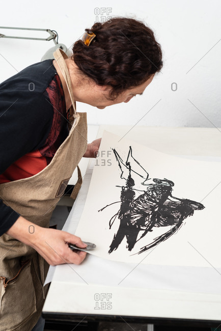 High angle side view of artisan female printmaker examining paper sheet with impression made in linocut technique while working in creative workshop