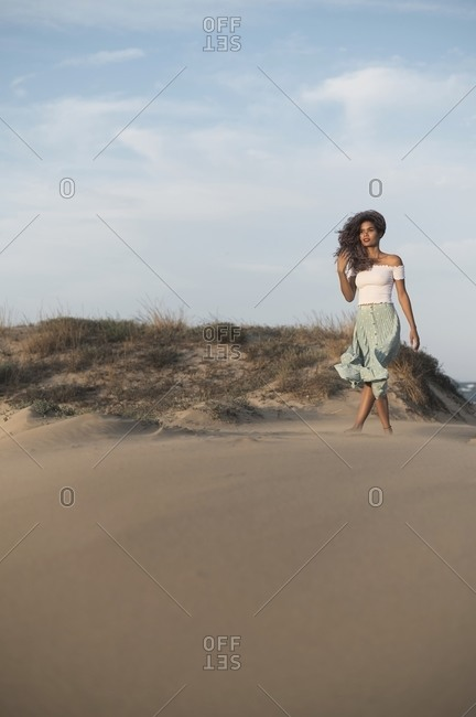 From below charming happy ethnic female in summer outfit walking along sandy hill on background of sundown in backlit and looking away