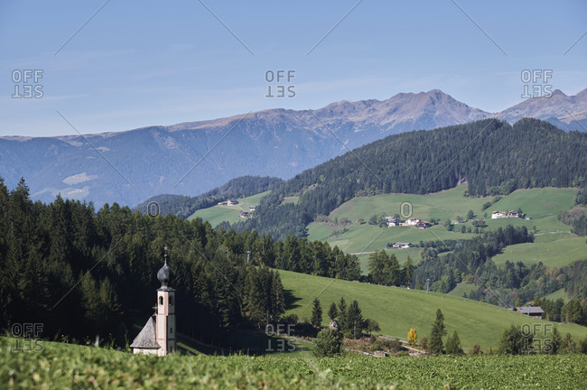 Picturesque scenery of alpine valley with houses and tower with dome against clear blue sky