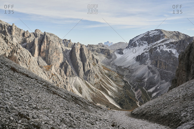 Amazing view of snowy mountains and valley in Dolomites on blue sky with clouds