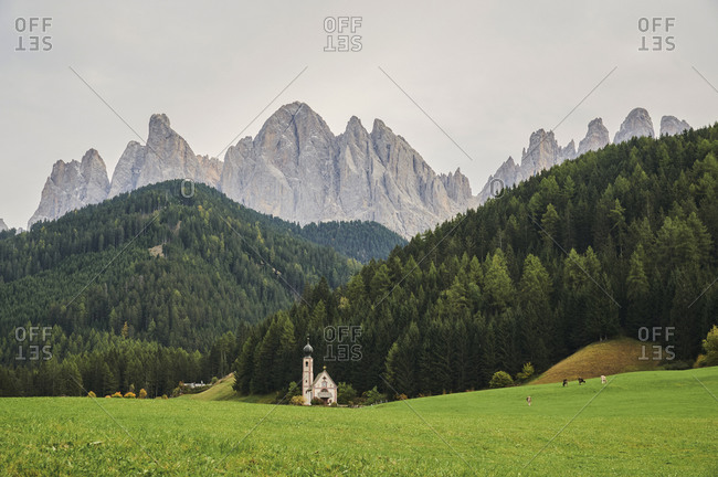 Picturesque scenery of alpine valley with tower with dome against cloudy sky
