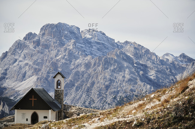 Spectacular scenery of small church with bell tower against rough mountain ridge at daytime
