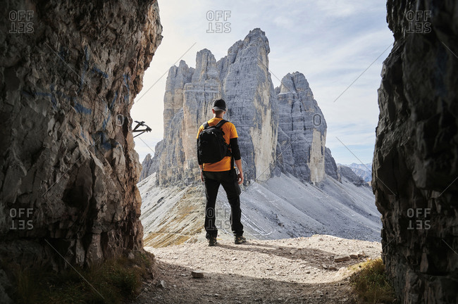 Back view of full length anonymous person in casual outfit with backpack standing on edge of rocky cliff and admiring magnificent landscape of mountainside