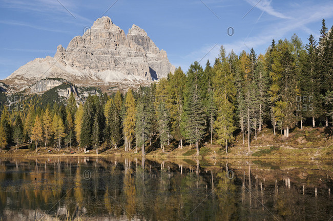 Amazing landscape of lake with calm water located near evergreen woods on sunny day on background of the Dolomites mountain range in Italy