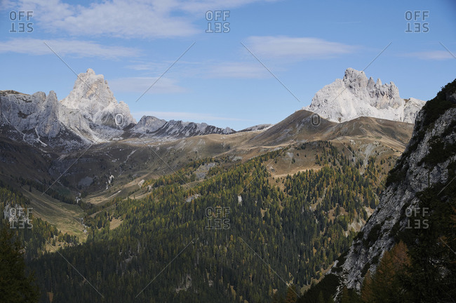 Picturesque scenery of high mountain in Dolomites under clouds near green coniferous forest under cloudy bright sky