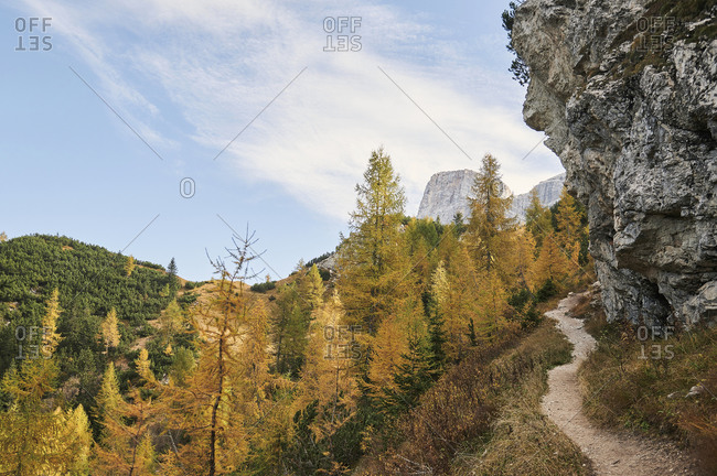 Scenic view of sandy road in the Dolomites mountain range near woods with green and yellow trees in fall in Italy