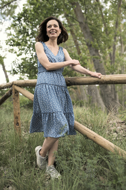 Cheerful young slender female in dress looking away while standing near simple wooden fence along narrow footpath between green trees in forest in daylight