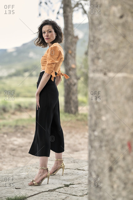 Side view full body of thoughtful young slender female in crop top and long black skirt looking at camera while standing between tall thick columns in park in daytime