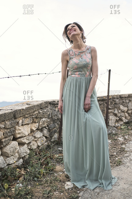 Full body of cheerful young skinny female in long festive dress looking up with bright smile while standing by stone fence under cloudless sky