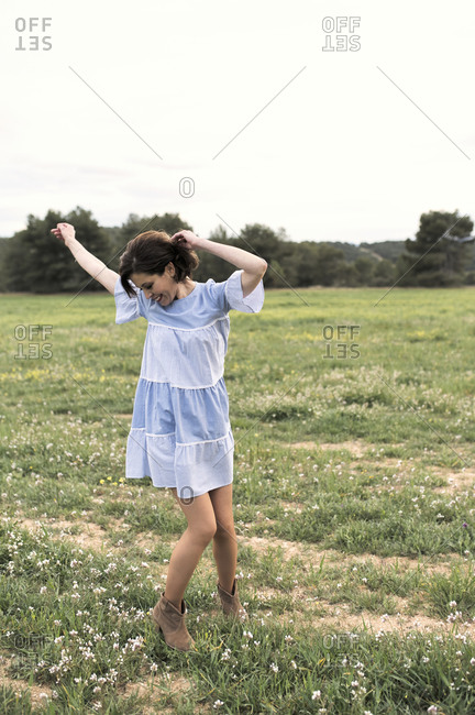 Delighted female in short blue dress walking through meadow covered with grass next to forest and mountain valley under cloudless sky in daytime looking at camera