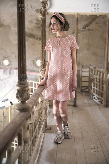Full body of thoughtful young slim female in pink polka dot dress and sneakers looking away while holding railing in bright spacious hall decorated in pastel colors