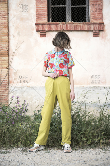 Full body of faceless female in shirt with floral print and light green trousers looking down while standing under window of old construction in daytime