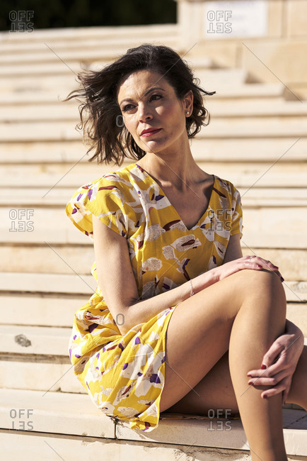 Side view of dreamy young slender female in short yellow summer dress looking away with hand at cheek while chilling on staircase in sunlight
